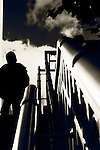 A silhouette of a young man on a walkway