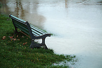 Park bench almost in the rising water of the Garonne River in Toulouse, France.