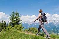 Single female hikes along trail in Austrian Alps with Steinernes Meer (Stone sea) mountain range in background