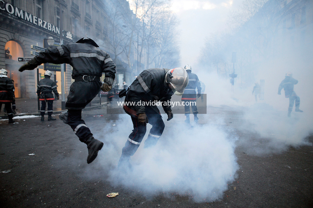25 March 2004 - Paris, FRA - Firefighters drown in tear-gas in Paris, France, 25 March 2004. The firefighters earlier marched through the city to demand that their profession be classified as a dangerous occupation which entails various social security benefits including early retirement. The confrontation with riot police left 2 firefighters and 20 policemen injured. Photo Credit: David Brabyn.