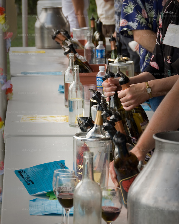 """Volunteers pour tastes of wine during the annual """"Key West Fest"""" wine and music festival at Breaux Vineyards in Northern Virginia.  (This photo was published by Destinations Magazine, journal of the American Bus Association, in October 2007.)"""