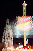 Oktoberfest, Munich, Germany, 2011. Long exposure of Starflyer 48 chain carousel tower and St. Paul Church at night.