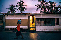 A man carries a plastic vessel of drinking water. Many houses on Ebeye do not have running water and most of its 13,000 plus population has to use rain water from water collection tanks or fetch it from a nearby fresh water pumping station. For one hour at a time every other day fresh water is pumped into the pipe delivery system to each section of the island at a time. Many houses have tanks that are used to store water between pumping episodes.