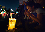 A girl prays after setting a floating candle lantern on the river on August 6, 2015, in Hiroshima, Japan. The lanterns, thousands of which were launched on the 70th anniversary of the atomic bombing of the city, carried handmade messages and drawings, conveying each person's prayers for peace and comfort for the victims of the violence.
