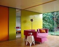 A vivid lime green and bright orange colour scheme creates a dramatic backdrop for a fuschia-pink L-shaped sofa