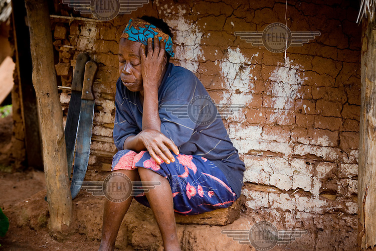 A women with two machetes behind her sits in front of her hut in a village located in the jungle of the Mbomou province.