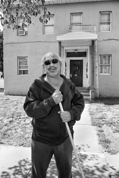 A man outside of his house in Port Jervis New York sweeping the sidewalk