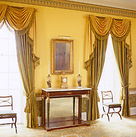 Elaborately swagged gold and green curtains adorn the floor to ceiling windows of the yellow drawing room