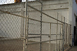 Chain link fence and gate enclosing a parking lot for an old industrial building downtown San Diego, CA