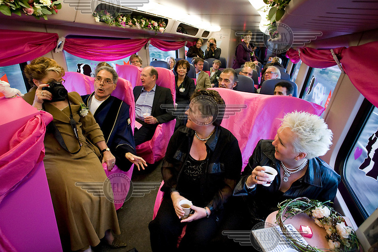 A guest takes a picture sitting on the registrar's lap of a lesbian couple getting married on a train, part of a campaign to get more Dutch people reading literature. All members of public libraries can have the book Two Women, by author Harry Mulisch, for free..