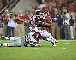 Alabama wide receiver Amari Cooper (9) is tackled by Ole Miss linebacker Mike Marry (52) and Ole Miss linebacker Serderius Bryant (14) and Ole Miss defensive back Cody Prewitt (25) at Bryant-Denny Stadium in Tuscaloosa, Ala. on Saturday, September 29, 2012. Alabama won 33-14. Ole Miss falls to 3-2.