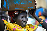 A displaced woman carries cooking oil on her head during a food distribution by the United Nations World Food Program in Agok, a town in the contested Abyei region where tens of thousands of people fled in 2011 after an attack by soldiers and militias from the northern Republic of Sudan on most parts of Abyei. Although the 2005 Comprehensive Peace Agreement called for residents of Abyei--which sits on the border between Sudan and South Sudan--to hold a referendum on whether they wanted to align with the north or the newly independent South Sudan, the government in Khartoum and northern-backed Misseriya nomads, excluded from voting as they only live part of the year in Abyei, blocked the vote and attacked the majority Dinka Ngok population. The African Union has proposed a new peace plan, including a referendum to be held in October 2013, but it has been rejected by the Misseriya and Khartoum.