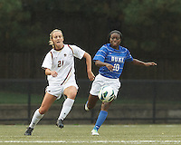 Boston College midfielder Kate McCarthy (21) controls the ball as Duke University midfielder Toni Payne (10) closes.Boston College (white) defeated Duke University (blue/white), 4-1, at Newton Campus Field, on October 6, 2013.