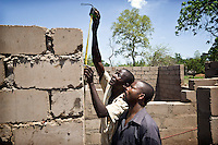 Constructors building a new health clinic for AMREF (African Medical and Research Foundation) in Tali Payam. Central Equatoria, South Sudan.