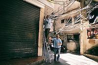 Men fixing electric wires In the Shatila camp as electricity shortage are frequent every day. This is due to the poor infrastructure and the dangerous wire hanging from the roofs, sometimes touching water leaks. Beirut. Lebanon. August 2015