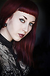 Portrait of a young female with long red hair wearing dark vampirish make up, and a black lace blouse, with pale skin, with simple interior background.