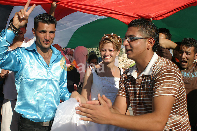 Mahmoud Ala'a El-deen and Sara Zwahreh celebrate their wedding ceremony during a protest against Israel's separation barrier in the West Bank village of Maasarah, near Bethlehem, Friday, July 31, 2009. The couples said they were there as a creative form of protest to show how hard it is for Palestinians to move around and live in the West Bank. Photo by Najeh Hashlamoun