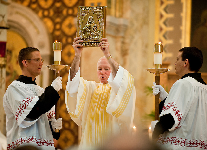 Deacon Tim Reilly carries  the Book of Gospels as walks to the ambo to proclaim the Gospel. (Sam Lucero photo)
