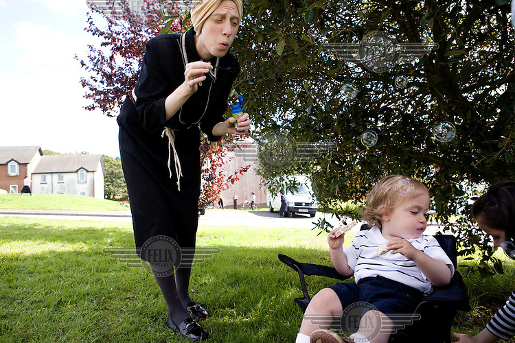 Pearl blows bubbles for her son on the lawn. Hasidic families stay in Pentre Jane Morgan university accommodation when they holiday in Aberystwyth. Every other day, bread, milk and other supplies are brought from Kosher shops in London and resold from one of the rented houses on the campus.