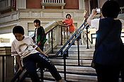 A child slides down while a tourist takes a picture of a woman inside the shopping centre of The Venetian Macau Resort Hotel in Macau, China.