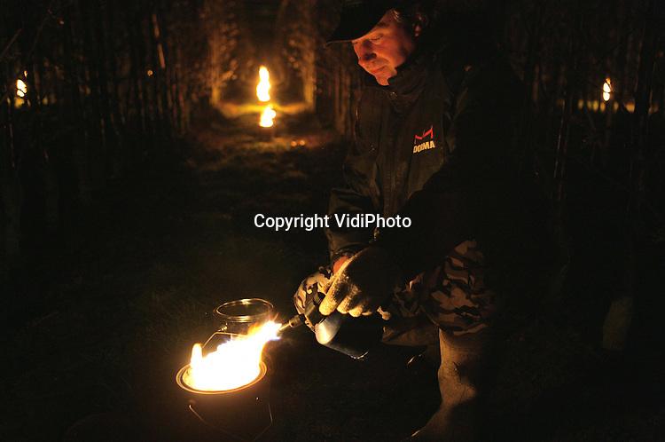 Foto: VidiPhoto..KESTEREN - Om te voorkomen dat de bloesem en de knoppen bevriezen, steekt fruitteler Machiel van Capel uit Kesteren dinsdagochtend de honderden vuurpotten onder zijn kersenbomen aan. De maatschap Van Capel is met ruim 3 hectare een van de grootste kersenboeren in de Betuwe. Steeds meer kersentelers gebruiken vuurpotten om schade door nachtvorst te bestrijden. Door de gestegen olieprijzen is dat inmiddels een kostbare zaak geworden. Het fenomeen is overgewaaid vanuit de druiventeelt in Frankrijk.