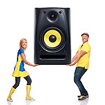 Smiling man and woman holding a large sound speaker in their hands. Musical equipment, entertainment concept. Isolated on white background.