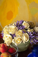 Rose 'Evening Star' in arrangement in front of yellow painting