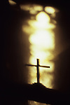 Shadow of crucifix standing on table or altar silhouetted against band of shimmering light from Gothic church window