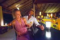 Maldives, Rangali Island. Conrad Hilton Resort. Couple in the bar at night. (MR)