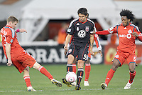 Jaime Moreno #99 of D.C. United makes a pass between Jacob Peterson #23 and Julian de Guzman #6 of Toronto FC during an MLS match that was the final appearance of D.C. United's Jaime Moreno at RFK Stadium, in Washington D.C. on October 23, 2010. Toronto won 3-2.