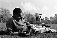 USA. New York. Central Park. Carlos (C) plays karate moves with his cousin Richie (R) on the ground, while a young black teenager from Spanish Harlem picks up grass.  The three adolescents are Puerto Ricans. 10.05.86 © 1986 Didier Ruef