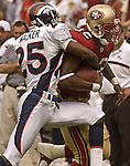 Denver Broncos defensive back Denard Walker (25) attempts to strip ball from San Francisco 49ers running back Kevan Barlow (32) on Sunday, September 15, 2002, in San Francisco, California. The Broncos defeated the 49ers 24-14.
