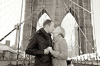 Sepia toned image of just engaged couple kissing on The Brooklyn Bridge.