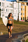 A young surfer carries her board down to the beach at Bondi.  Bondi Beach, Sydney, New South Wales, AUSTRALIA.