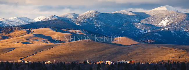 Last rays of sunlight in late winter on the downtown area of Missoula, Montana. The North Hills and snow covered mountains beyond the city