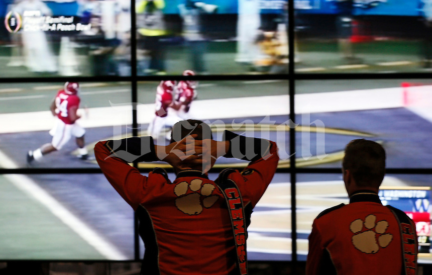 Members of the Clemson marching band watch as Alabama scores a touchdown against Washington in the Peach Bowl prior to the other College Football Playoff semifinal Fiesta Bowl against the Ohio State Buckeyes at University of Phoenix Stadium in Glendale, Arizona on Dec. 31, 2016. (Adam Cairns / The Columbus Dispatch)