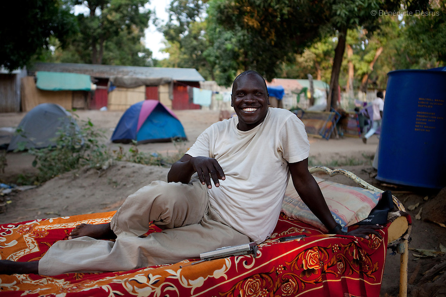 14 december 2010 - Juba, South Sudan - Peter Remy, 41 years old, sits on his bed on the bank of the river Nile in the southern capital Juba, South Sudan. He returned to the South after spending 21 years in Khartoum, bringing with him all his family's possessions, including eight beds, 16 chairs and a television. Over 55.000 southerners have returned to the South in advance of the january 9, 2011 referendum on the independence of the South. The return has been organized by the autonomous Government of Southern Sudan programs and others haves spontaneously returned to various states across the south. Many Southern Sudanese fled to the north during the second north-south civil war, which began in 1983 and ended with a 2005 peace deal that granted the south the right to secede through a referendum. Photo credit: Benedicte Desrus