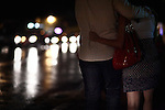 A couple walks in the rain, backlighted by headlights and wet streets, during First Friday celebrations in the Southtown arts district, Friday, Sept. 4, 2009, in San Antonio, Texas. (Darren Abate/pressphotointl.com)