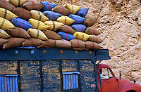 Man driving a truck loaded with colorful sacks.