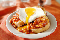 Baked beans and fried egg on buttered crumpets stock photos