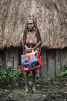 Lemeke Loke, who is over 90 years old, near her house with a 'Spider Man' bag, which she uses to collect vegetables from her garden.