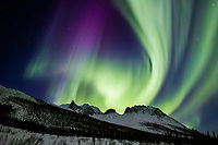 Aurora borealis swirls across the sky over the Brooks mountain range, Snowden mountain, arctic Alaska.