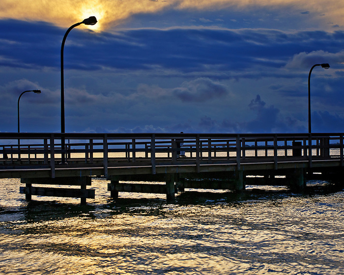 Sun peaks through to light the lamp on the new pier at Captree State Park