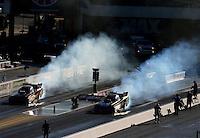 Sep 19, 2015; Concord, NC, USA; NHRA funny car driver Alexis DeJoria (left) does a burnout alongside Cruz Pedregon during qualifying for the Carolina Nationals at zMax Dragway. Mandatory Credit: Mark J. Rebilas-USA TODAY Sports