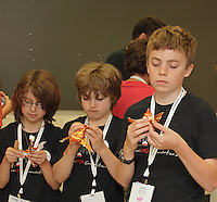 Three young students concentrating on folding a complex origami dragon. Nathan Ascher (back center) teaches a complex origami dragon design by Diego Fernando Becerra Ramirez to a clas at OrigamiUSA 2013