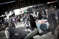 A Kashmiri Muslim woman walks in a street market in Sopore, north of Srinagar, stronghold of the Islamist anti-India movement, declared steadily under curfew. The civilian resistance in the town is sprawled out and the stone pelting sparks fiercely on its streets. According to non governmental observers, the rate of human rights violations and atrocities, like rape and abductions by Indian army and paramilitary against the Muslim population, is very high in the region. Sopore town, Indian administrated Kashmir.