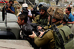 Israeli soldiers detain a Palestinian boy during a protest in support of Palestinian prisoners on hunger strike in Israeli jails at the al-Aroub Palestinian refugee camp, just north the West Bank town of Hebron on May 31, 2014. Photo by Mamoun Wazwaz