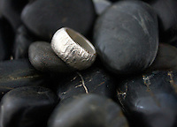silver wide engraved band against black pebbles