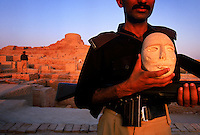 Tourists who come to Mohenjo Daro always get an armed escort.  Bandits and kidnappers are a problem in Sindh province.  One of the guards holds an artifact from the Mohenjo Daro museum.   4,800 years ago, at the same time as the early civilizations of Mesopotamia and Egypt, great cities arose along the flood plains of the Indus and Saraswati (Ghaggar-Hakra) rivers.  Developments at Harappa have pushed the dates back 200 years for this civilization, proving once and for all, that this civilization was not just an offshoot of Mesopotamia..They were a highly organized and very successful civilization.  They built some of the world's first planned cities, created one of the world's first written languages and thrived in an area twice as large as Egypt or Mesopotamia for 900 years (1500 settlements spread over 280,000 square miles on the subcontinent)..There are three major communities--Harappa, Mohenjo Daro, and Dholavira. The town of Harappa flourished during this period because of it's location at the convergence of several trade routes that spanned a 1040 KM swath from the northern mountains to the coast.