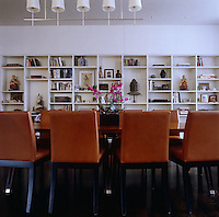 The far wall of the living space beyond the dining area is dominated by a row of built-in shelves